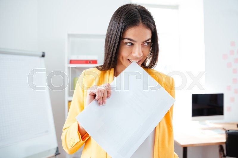 Stock image of 'Attractive businesswoman standing with paper in office and looking away'