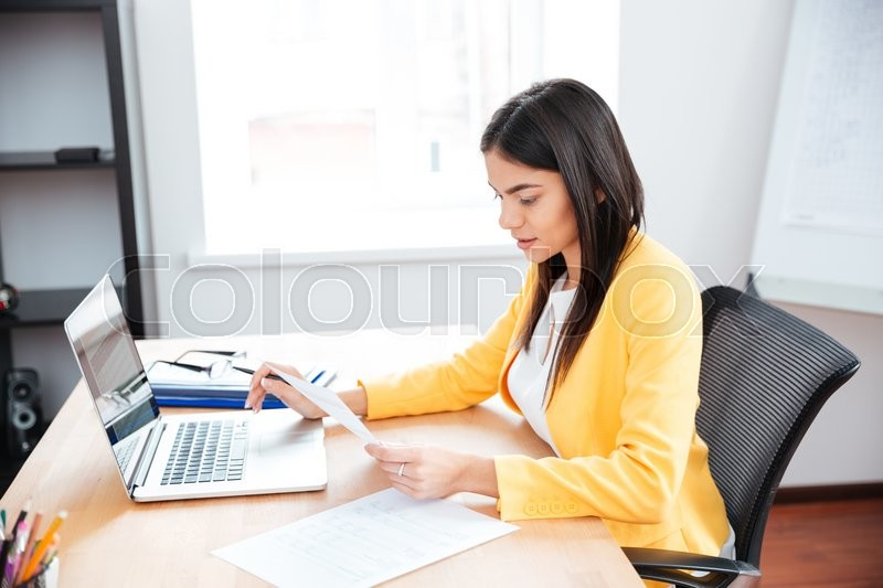 Stock image of 'Beautiful businesswoman working with papers and laptop computer in office'