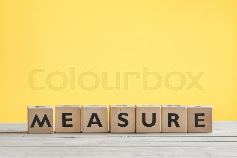 Stock image of 'Measure sign with wooden cubes on a yellow background'