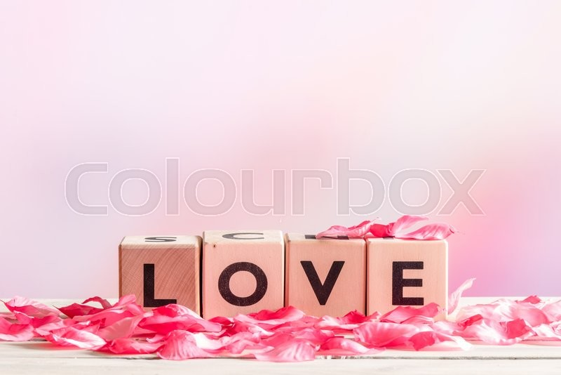 Stock image of 'Love sign made of wood with rose leaves'