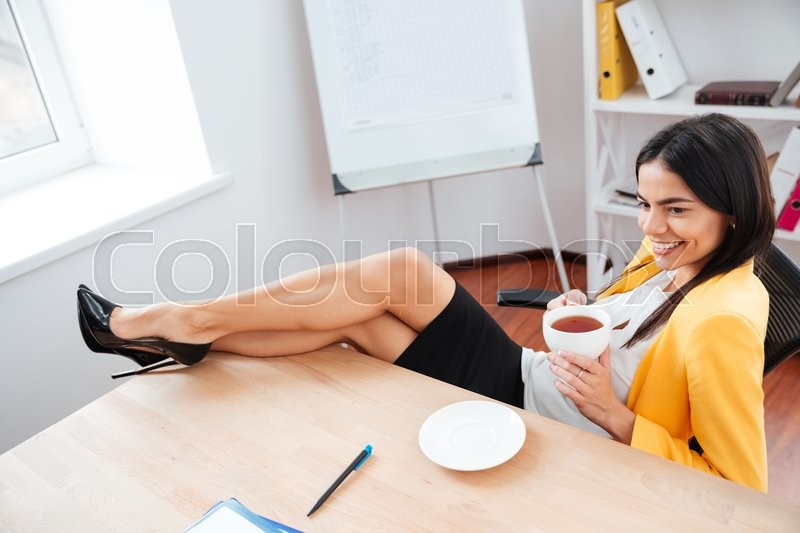Stock image of 'Happy businesswoman resting with legs on the table and drinking coffee in office'