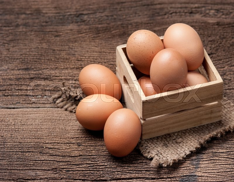 Stock image of 'Eggs on wooden table background'