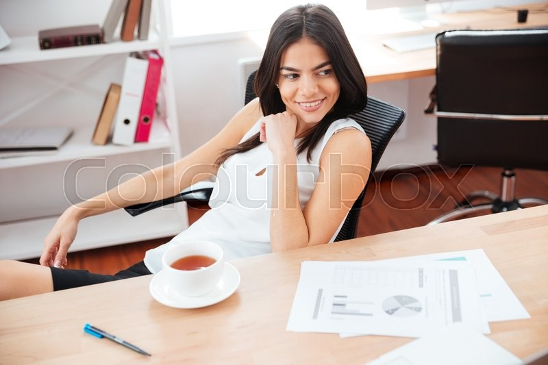 Stock image of 'Happy businesswoman sitting at the table with coffee and looking away in office'