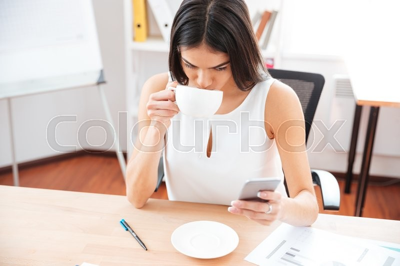Stock image of 'Young businesswoman drinking coffee and using smartphone in office'
