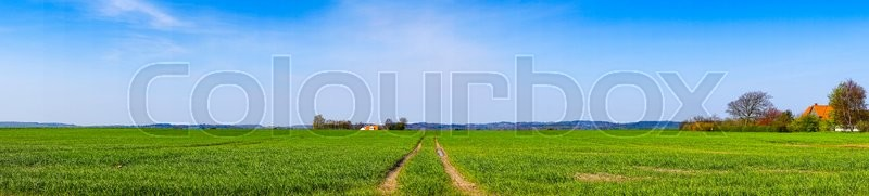 Stock image of 'Tracks on a field in panorama landscape with a farm'