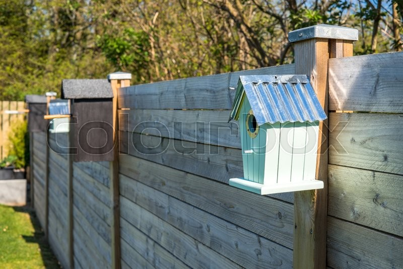 Stock image of 'Bird houses on a row at a fence in the spring'