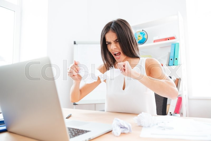 Stock image of 'Angry businesswoman working with laptop and papers in office'