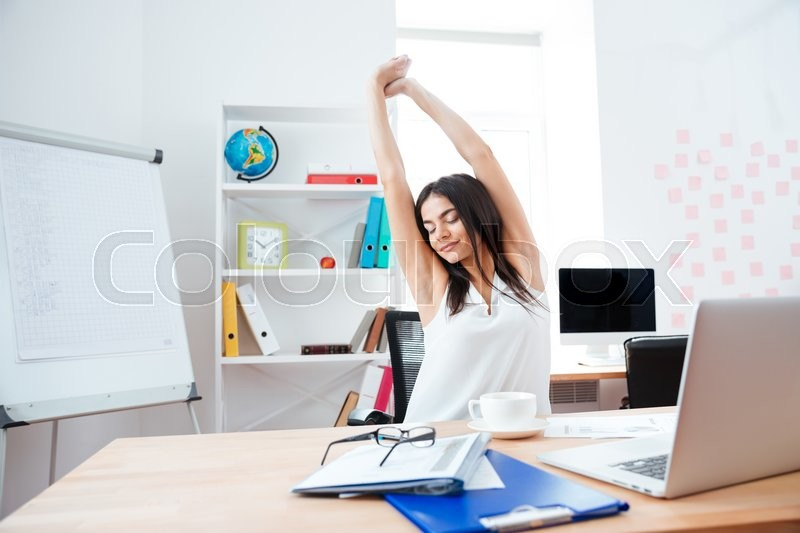 Stock image of 'Beautiful businesswoman stretching hands in office'
