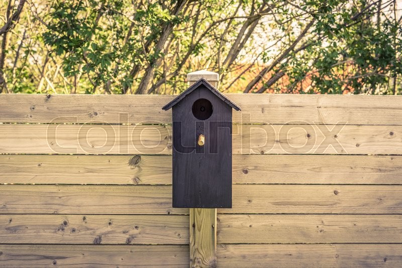 Stock image of 'Black bird house on a fence in the summer'
