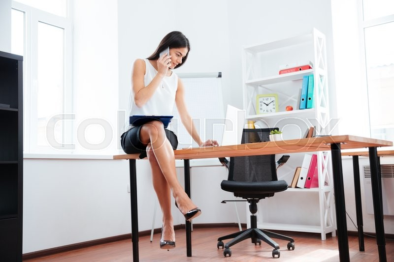 Stock image of 'Businesswoman sitting on the table and working with phone and laptop computer in office'