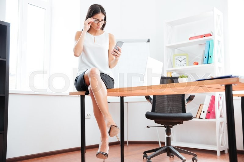 Stock image of 'Businesswoman sitting on the table and using smartphone in office'