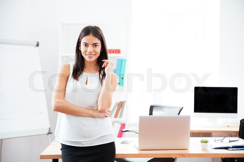 Stock image of 'Happy businesswoman standing in office and looking at camera'