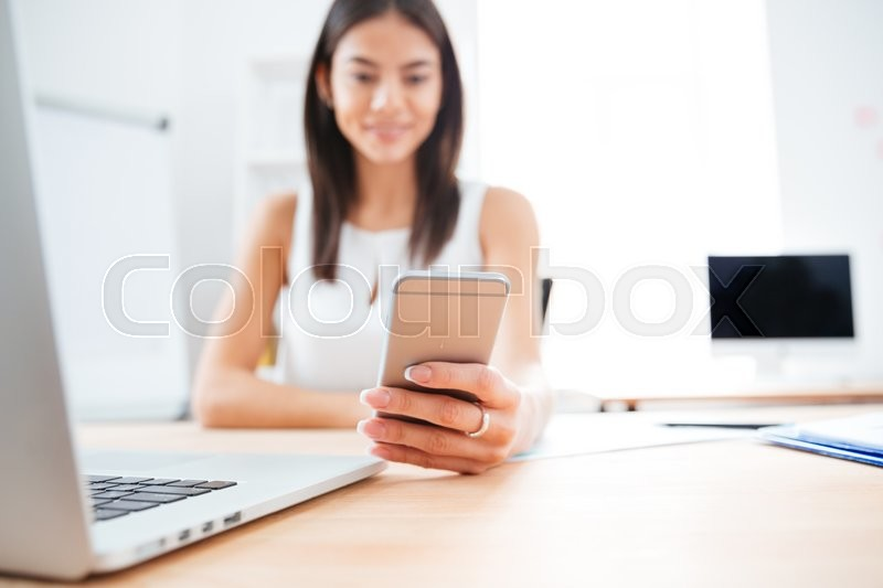 Stock image of 'Happy businesswoman using smartphone in office. Focus on smartphone'