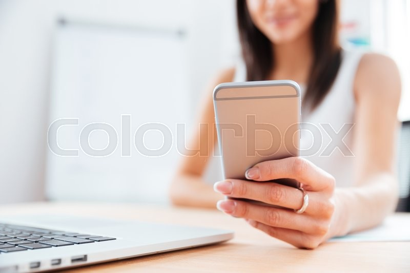 Closeup portrait of a female hands using smartphone in office. Focus on smartphone, stock photo