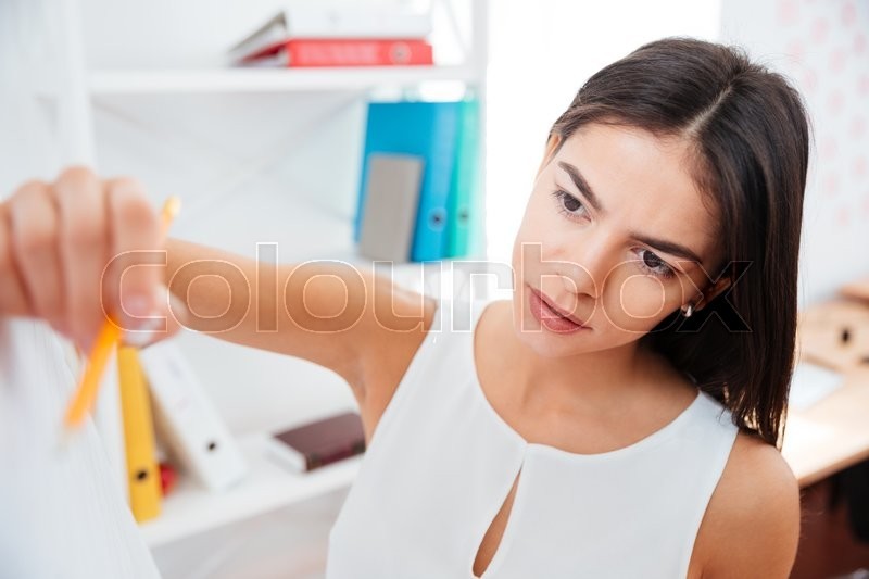 Stock image of 'Beautiful businesswoman writing on whiteboard in office'
