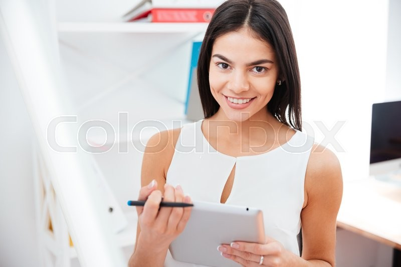 Stock image of 'Happy businesswoman holding tablet computer in office and looking at camera'