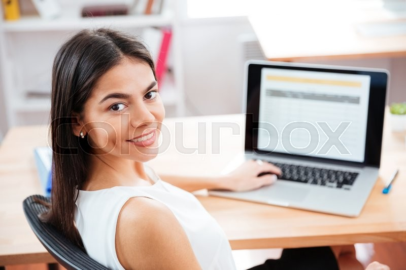 Stock image of 'Smiling businesswoman sitting at the table with laptop computer in office and looking at camera'