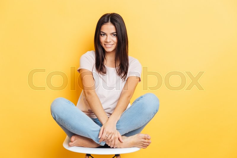 Stock image of 'Smiling lovely woman sititng on the chair over yellow bakground and looking at camera'
