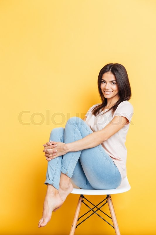 Stock image of 'Smiling attractive woman sitting on the chair over yellow background'