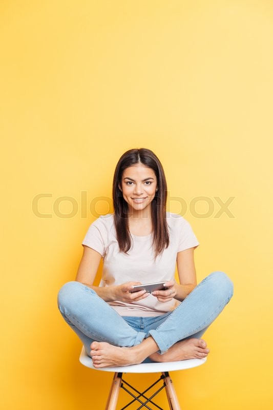 Stock image of 'Smiling casual woman sitting on the table and using smartphone over yellow background'