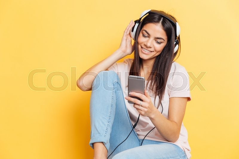 Stock image of 'Smiling woman listening music in headphones and using smartphone over yellow background'