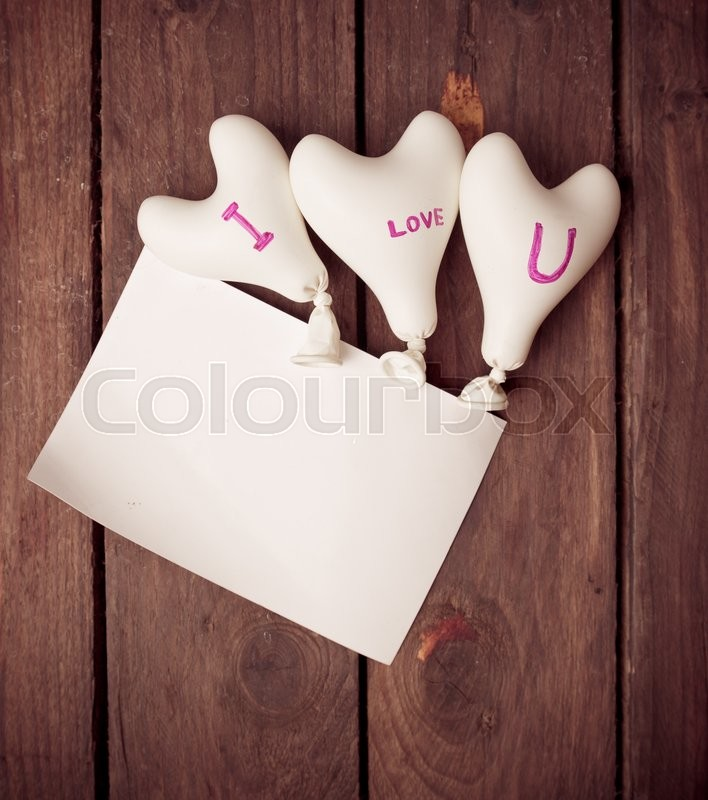 Stock image of 'Valentine day concept.heart balloon with blank notepape on wood,vintage color toned image'