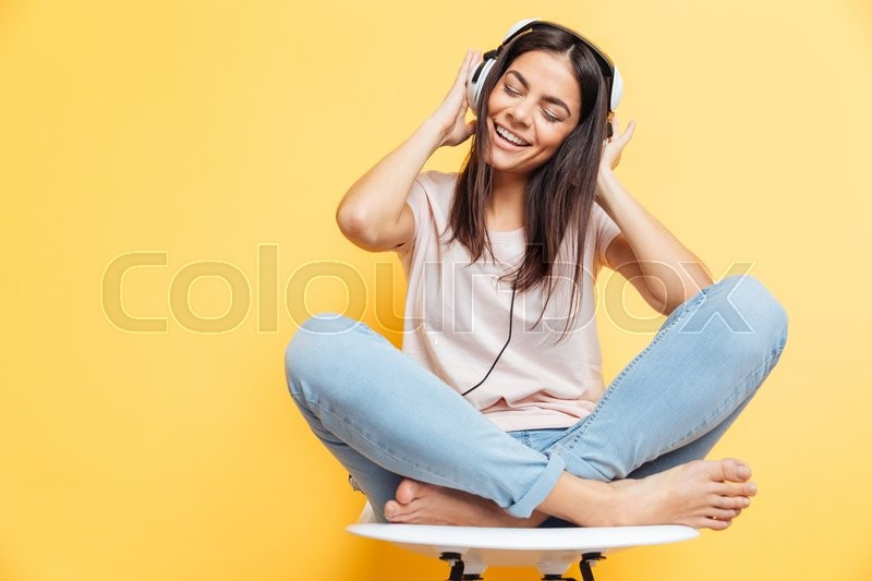 Stock image of 'Cheerful woman listening music in headphones over yellow background'