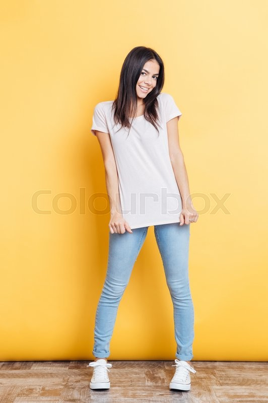 Stock image of 'Full length portrait of a smiling casual woman posing on yellow background'