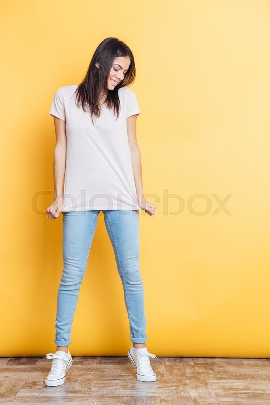 Stock image of 'Full length portrait of a happy casual woman posing on yellow background'