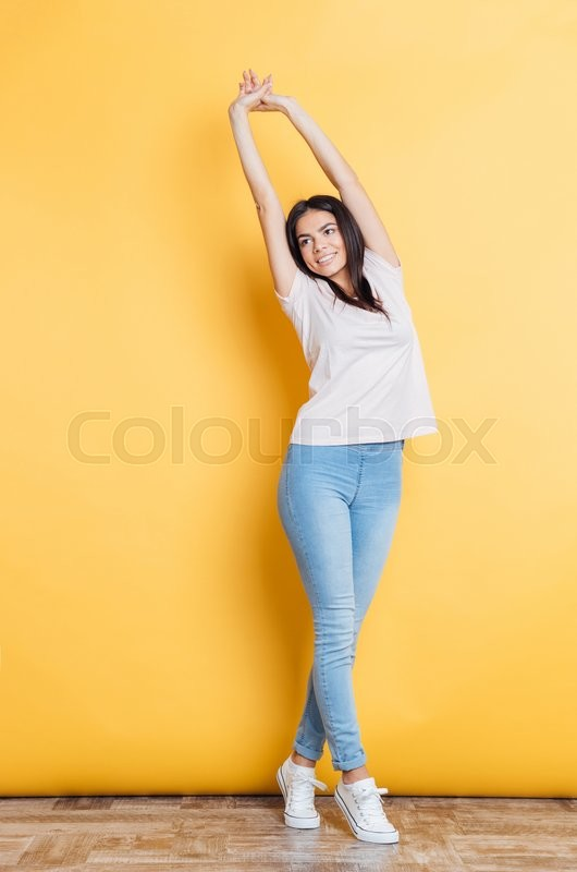 Stock image of 'Full length portrait of a smiling woman stretching hands on yellow background'