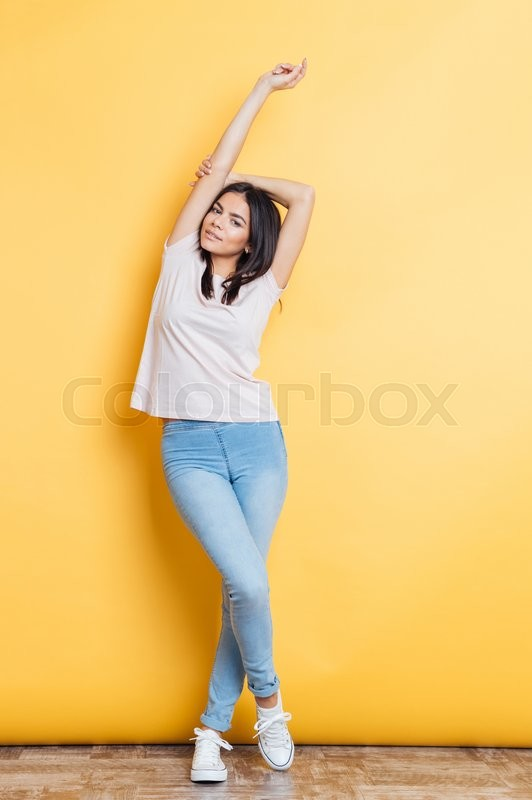 Stock image of 'Full length portrait of a stylish woman posing on yellow background'