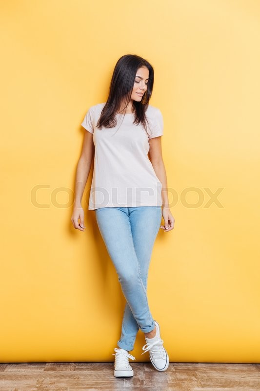 Stock image of 'Full length portrait of a lovely woman posing on yellow background'