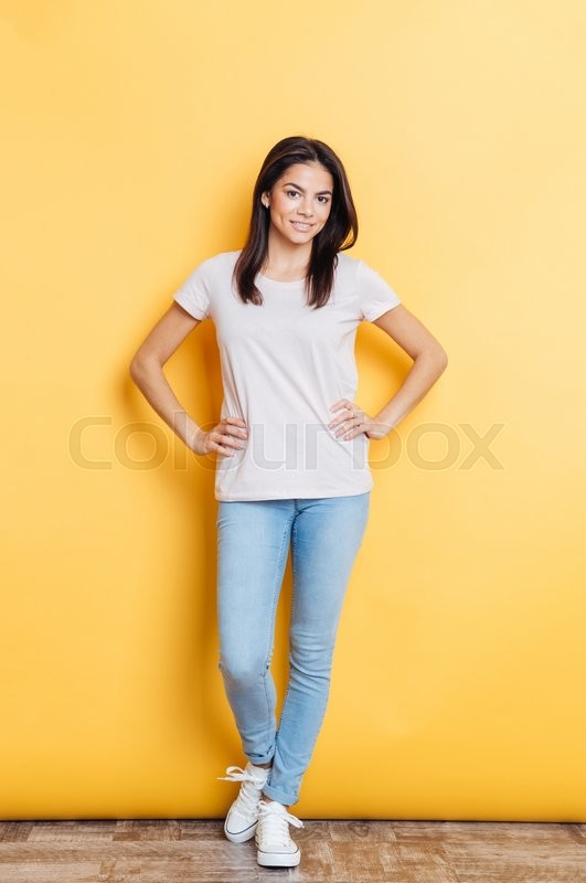 Stock image of 'Full length portrait of a smiling casual woman standing on yellow background and looking at camera'