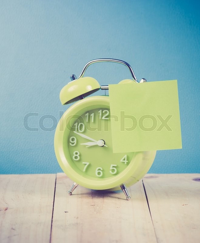 Stock image of 'Green alarm clock and sticky paper with Text Space on wood,blue background'