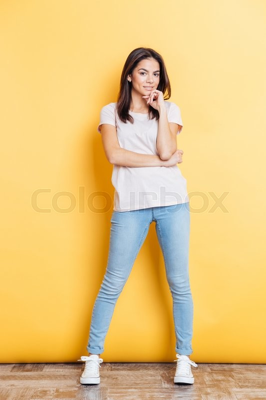 Stock image of 'Full length portrait of a happy beautiful woman looking at camera over yellow background'
