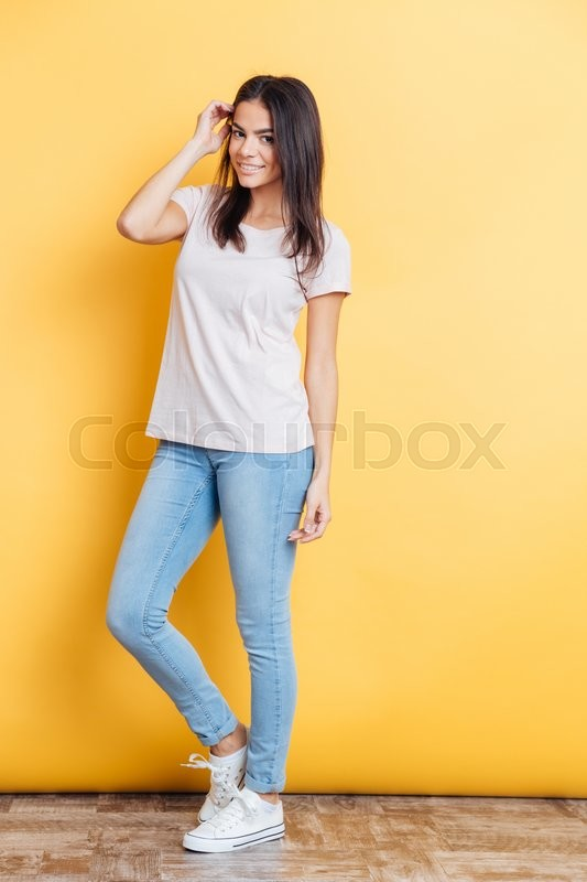 Stock image of 'Full length portrait of a happy attractive woman standing on yellow background'