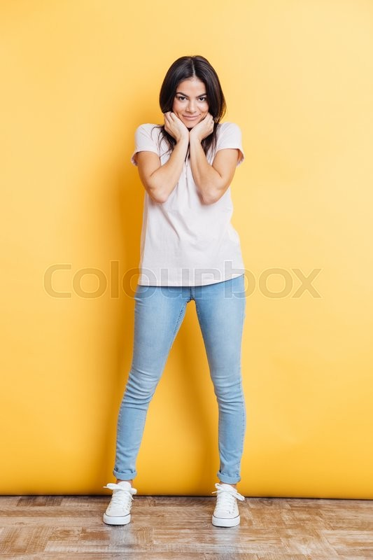 Stock image of 'Full length portrait of a pretty woman posing on yellow background'