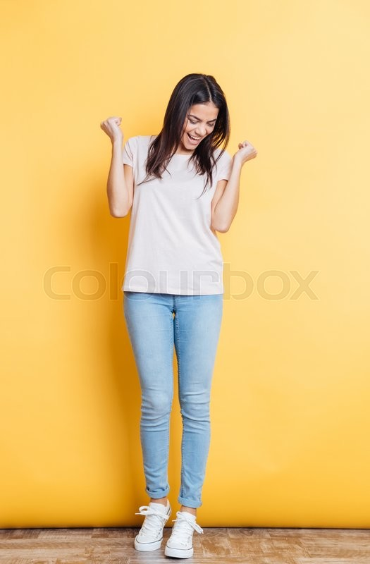 Stock image of 'Full length portrait of a successful woman standing on yellow background'