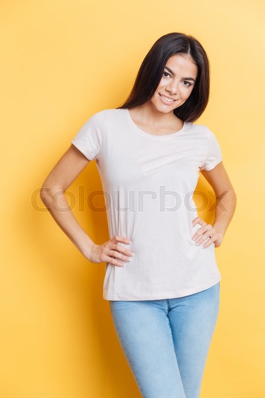 Stock image of 'Smiling casual woman standing over yellow background and looking at camera'