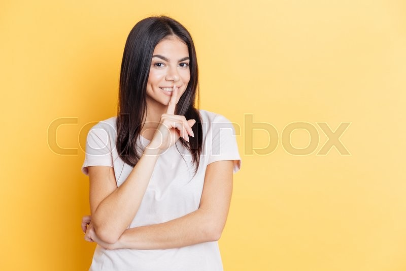 Stock image of 'Pretty woman showing finger over lips on yellow backgound'