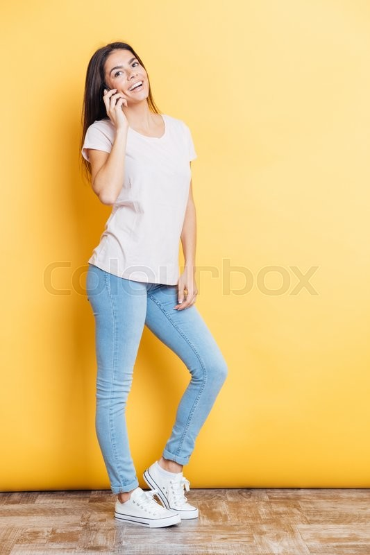 Stock image of 'Full length portrait of a smiling woman talking on the phone over yellow background'