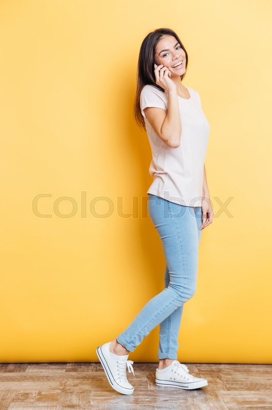Stock image of 'Full length portrait of a laughing woman talking on the phone and looking at camera over yellow background'