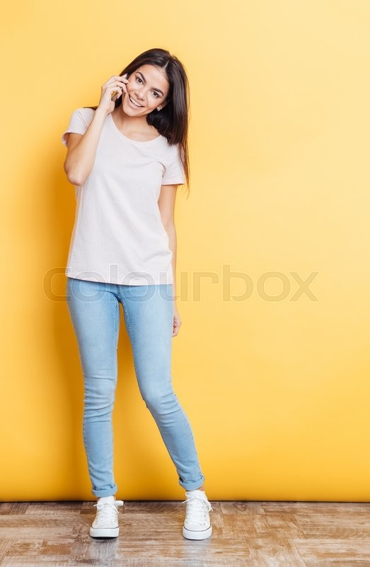 Stock image of 'Full length portrait of a pretty woman talking on the phone and looking at camera over yellow background'