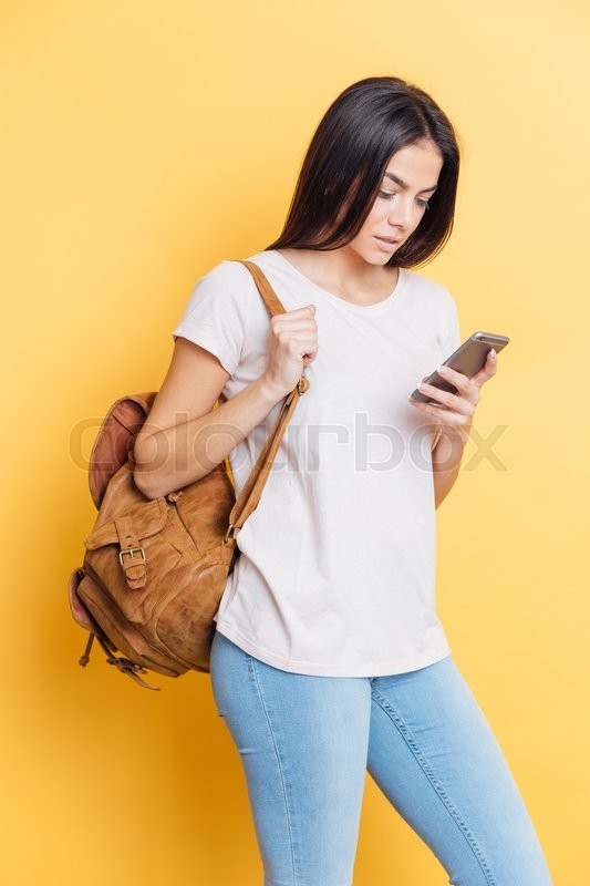 Stock image of 'Female student with backpack using smartphone over yellow background'