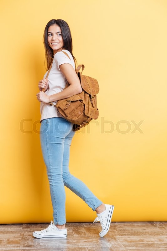Stock image of 'Full length portrait of a charming woman with backpack posing on yellow background '