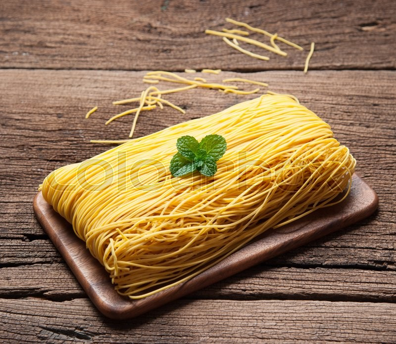 Stock image of 'Egg noodles on wood background'
