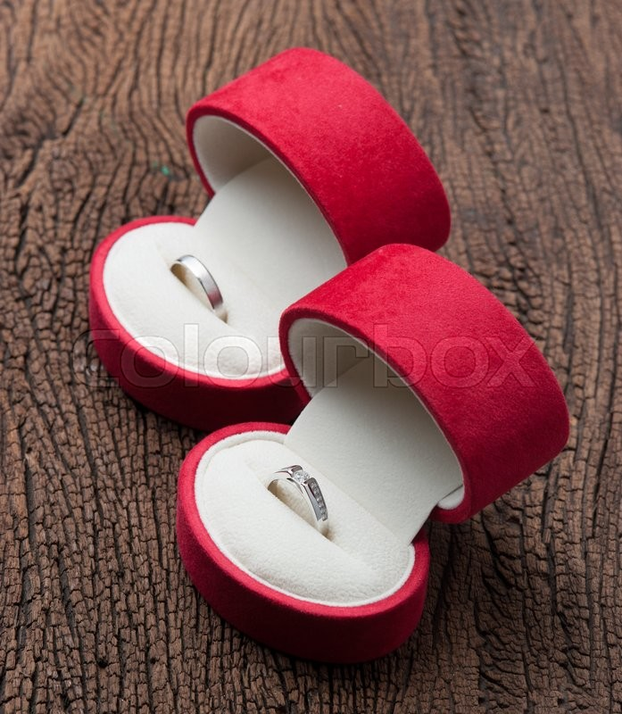 Stock image of 'Diamond ring in red velvet box on wood'