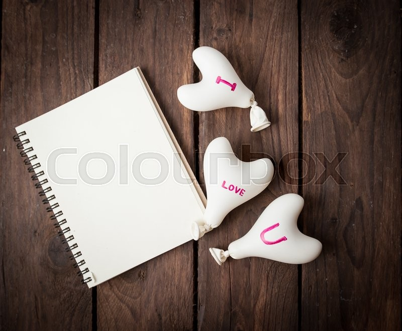 Stock image of 'Valentine day concept.heart balloon with notebook on wood'