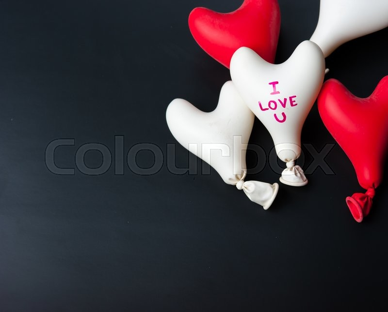 Stock image of 'Valentine day concept.red and white heart balloon on a black slate'