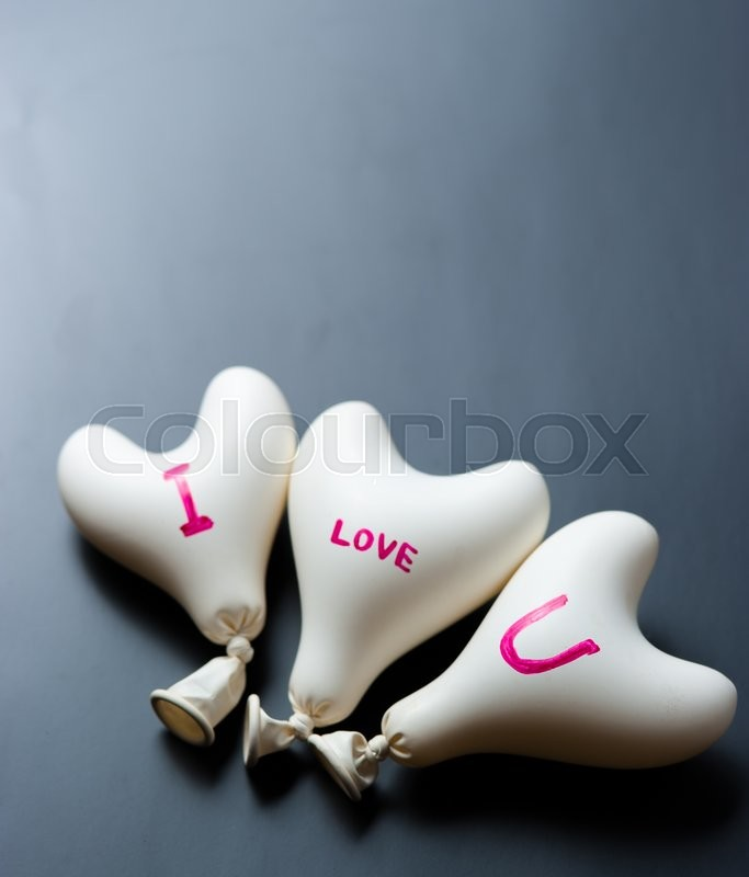 Stock image of 'Valentine day concept.white heart balloon on a black slate'